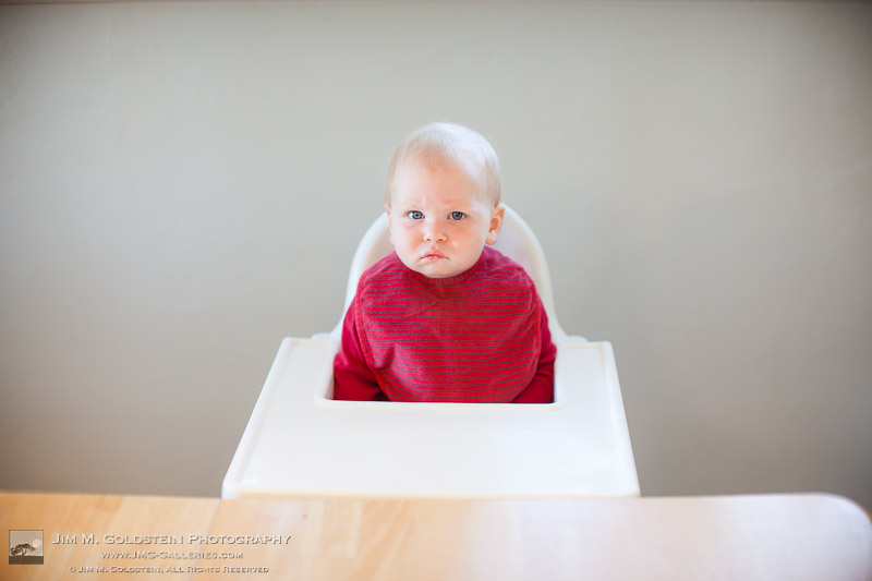 1 year old boy makes a serious face in his high chair waiting for his birthday cake