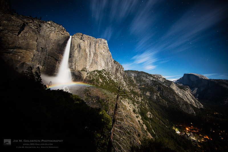 A moonbow spans across upper Yosemite Falls with passing clouds and Half Dome in view.