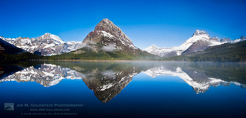 Fog forms over Swiftcurrent Lake and Mount Grinnell at sunrise in Glacier National Park, Montana